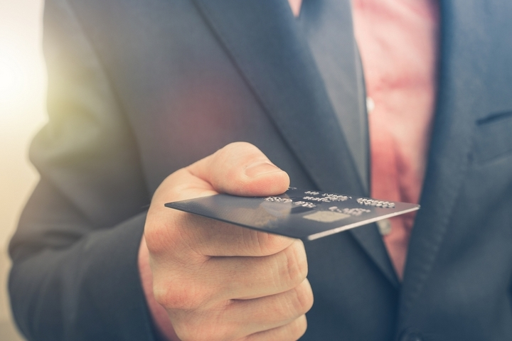 Paying By Credit Card Concept with Businessman Keeping Credit Card in His Hand.